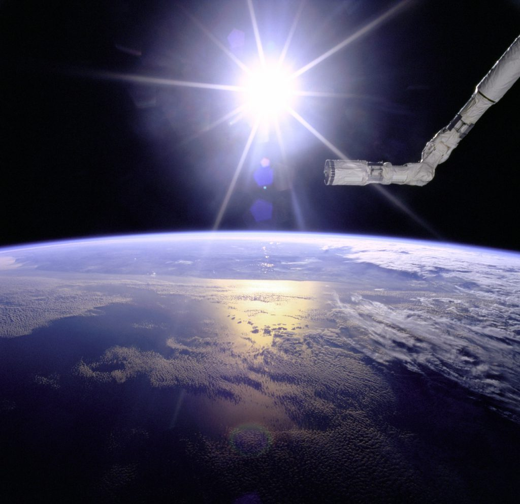 View of the Remote Manipulator System (RMS) end effector over an Earth limb with a solar starburst pattern behind it